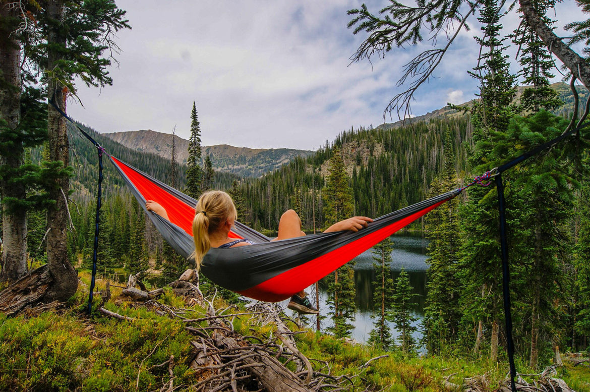 woman relaxing in a hammock in the woods