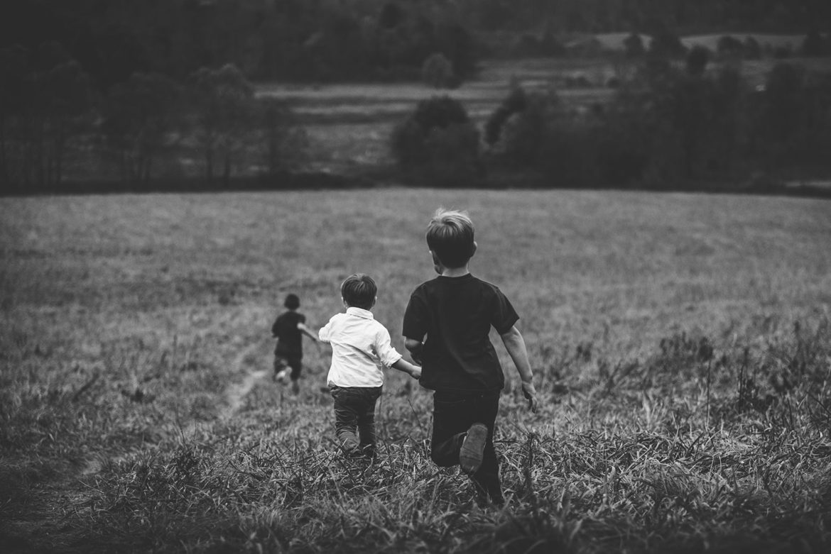 Boys Running Away from the Camera in a Field